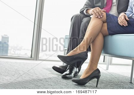 Low section of businessman flirting with female colleague in office