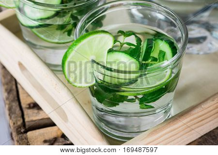 Glasses with detox infused cucumber water with lime and mint on wooden tray pitcherclose upspring summer