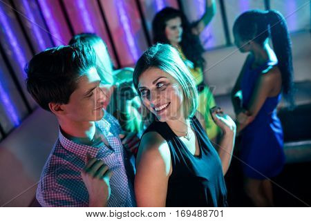 Smiling friends dancing on dance floor in bar