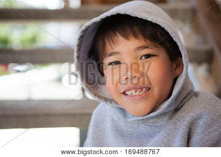Cute Asian boy smiling and wearing a hoodie to stay warm in cool weather