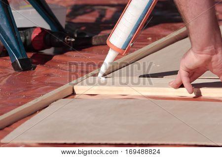 A carpenter using a glue gun on wood