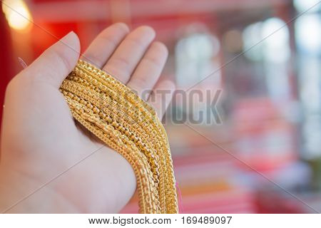 Gold neclace in hand blurr background with space jewelry