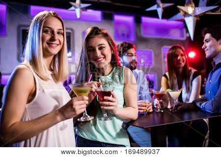 Portrait of smiling friends having cocktail at bar counter in bar