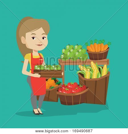 Caucasian worker of grocery store standing in front of section with vegetables and fruits. Female worker of grocery store holding a box with apples. Vector flat design illustration. Square layout.