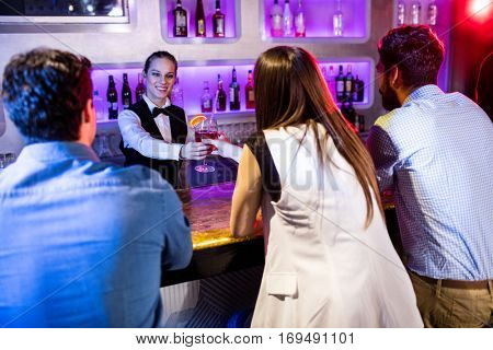 Barmaid serving drink to woman at bar counter in bar