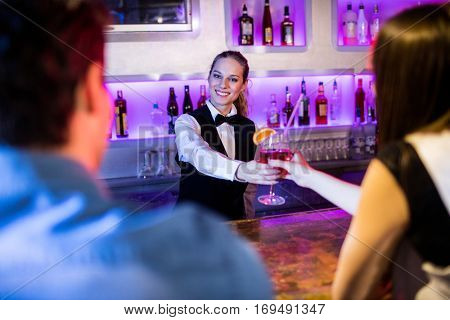Portrait of barmaid serving drink to woman at bar counter in bar