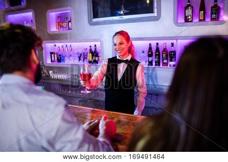 Portrait of barmaid serving drink to man at bar counter in bar