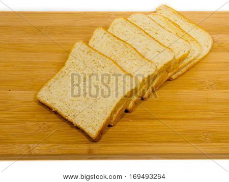 Side view of slices of toast bread on breadboard wooden, isolated on white background.