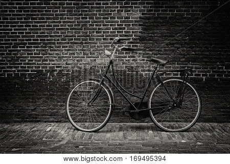Vintage bike against grunge old brick wall (Black and white)
