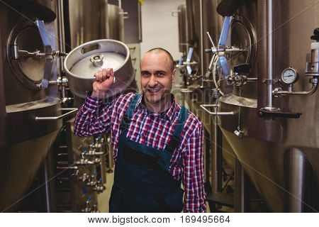 Portrait of confident male manufacturer carrying kegs at brewery