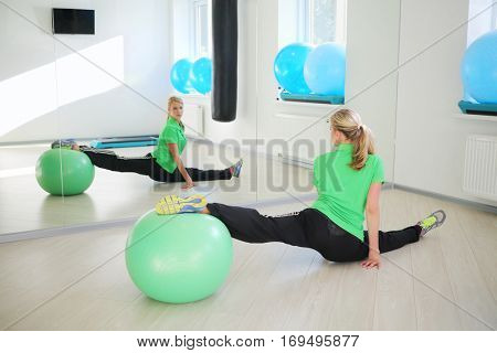 Happy young woman does exercise with fitball in fitness center in sunny room