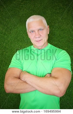 Middle-age muscular man in t-shirt stands near green wall with crossed arms