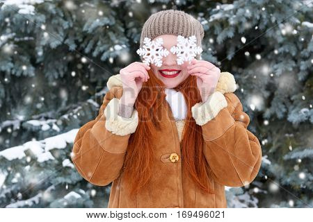 beautiful woman on winter outdoor posing with big snowflake toys, holiday concept, snowy fir trees in forest, long red hair, wearing a sheepskin coat