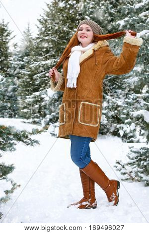 beautiful woman full length on winter outdoor, snowy fir trees in forest, long red hair, wearing a sheepskin coat