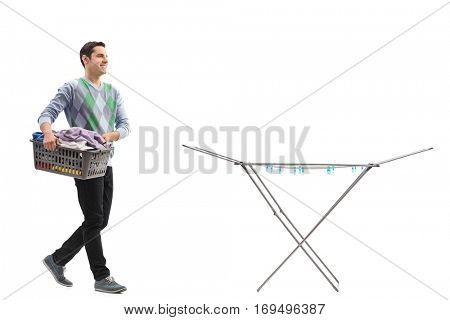 Full length portrait of a man holding a laundry basket full of clothes and walking towards a clothing rack dryer isolated on white background