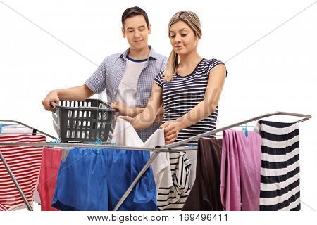 Guy holding an empty laundry basket with a woman picking up clothes from a clothing rack dryer isolated on white background
