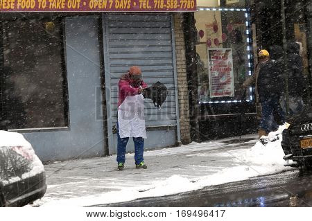 BRONX NEW YORK - JANUARY 7: Chinese woman spreading salt in front of business during snow storm. Taken January 7 2017 in New York.