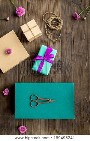 wrapping gifts in box for holiday top view mock up on wooden background