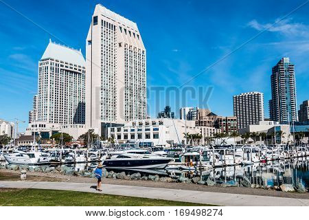 SAN DIEGO, CALIFORNIA - JANUARY 8, 2017:  Tourist walking on pathway at Embarcadero Marina Park North near Seaport Village with surrounding hotels and city skyline.