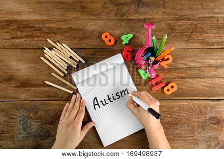 Autism. Hands writing the word in notebook on wooden background