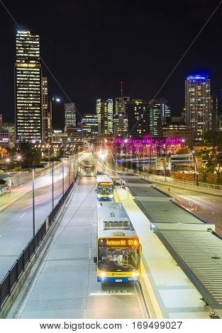Brisbane, Australia - September 26, 2016: Multiple exposure image of skyscrapers and light trail of buses at bus station in downtown Brisbane city at night.