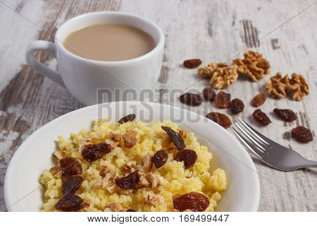 Cooked millet groats with raisins and walnuts on white plate cup of coffee with milk concept of healthy food nutrition and nutritious breakfast