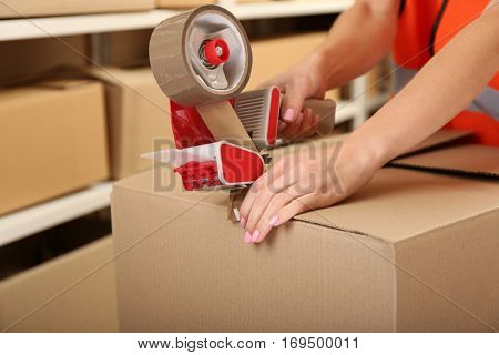 Female hands packing box at warehouse, closeup
