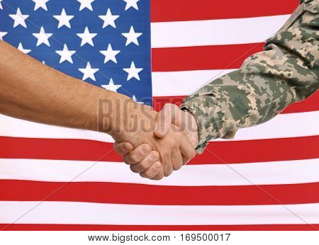 Soldier and civilian shaking hands with USA flag on background. Civilians protection concept