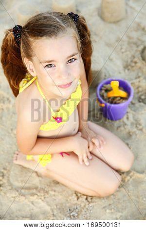 Cute girl building sandcastle on beach