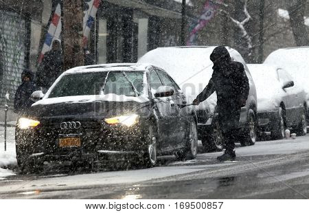 BRONX NEW YORK -JANUARY 7: Man cleaning car during snow storm. Taken January 7 2017 in New York.