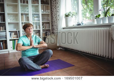 Senior woman meditating in prayer position at home