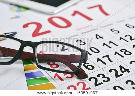 closeup of a pair of eyeglasses and a 2017 calendar on an office desk full of charts