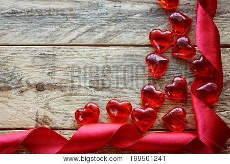 Valentine's Day background with scarlet ribbon glass heart on old wooden boards