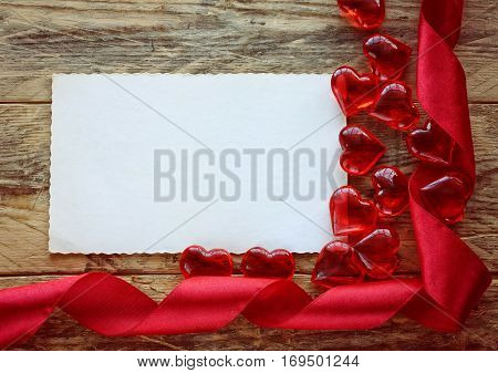 Valentine's Day background with scarlet ribbon glass heart empty paper on old wooden planks