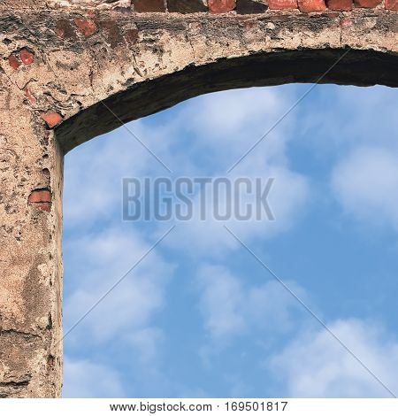 Barn gate door arch and sky stone wall closeup vertical bright white summer clouds cloudscape copy space background plastered grunge red brick stonewall pattern old aged weathered beige lime plaster texture natural grungy textured reddish vintage rough ru