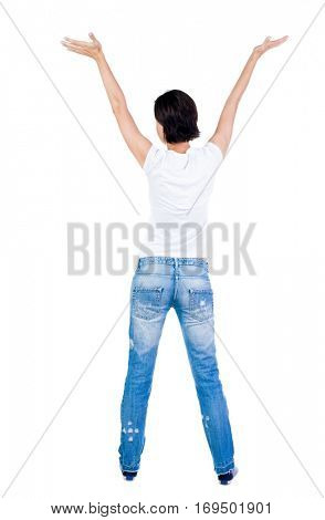 Back view of Beautiful woman in jeans looking at wall and Holds  hand up.  young brunette girl standing. Rear view people. Isolated over white background.