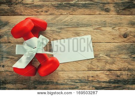 two red dumbbell with gift bow blank paper label on a wooden planks sport holiday concept