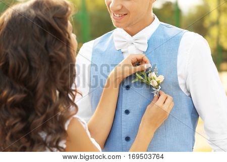 Bride pinning buttonhole to groom waistcoat, close up view