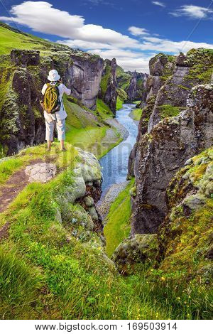 The elderly woman standing on a rock and photographing the scenic landscape. The concept of active northern tourism. The striking canyon in Iceland. Green Tundra in summer