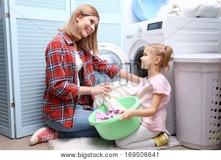 Pretty woman and her daughter doing laundry at home
