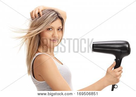 Young woman using a hairdryer isolated on white background