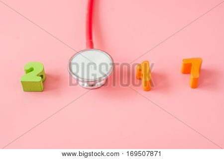 Red Stethoscope with 2017 on pink background.