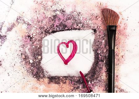 Makeup brush and lip gloss on white marble background, with traces of powder and blush forming a frame with a heart in it. 'Love Makeup' valentine design