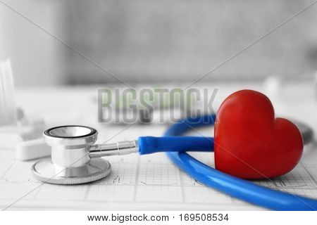 Stethoscope, pills and red heart with paper electrocardiogram
