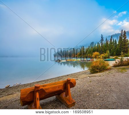Bench on the shore of Pyramid Lake. Cold foggy morning in the Rocky Mountains, Jasper National Park