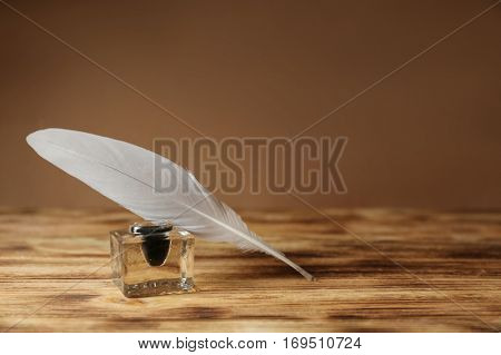 Feather pen and inkwell on brown background