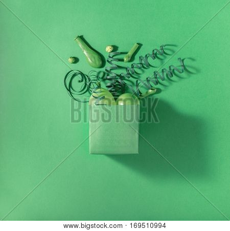Green gift box with green balloons and green streamers on a green background. Flat lay