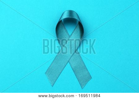 Sea-green ribbon on color background. Ovarian cancer and gynecological disorders concept