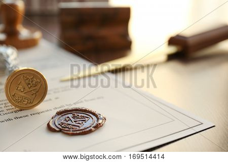 Old notarial wax stamp and office knife on document, closeup