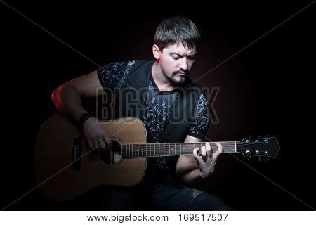 Portrait of a young bearded guitarist clamping chord on an acoustic guitar on a black background